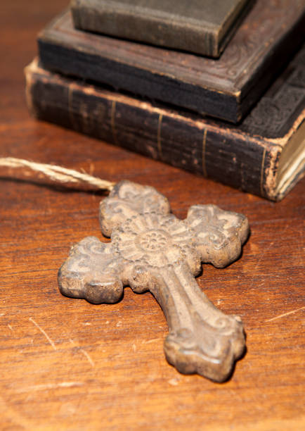 Cross with antique books on a wooden desk stock photo