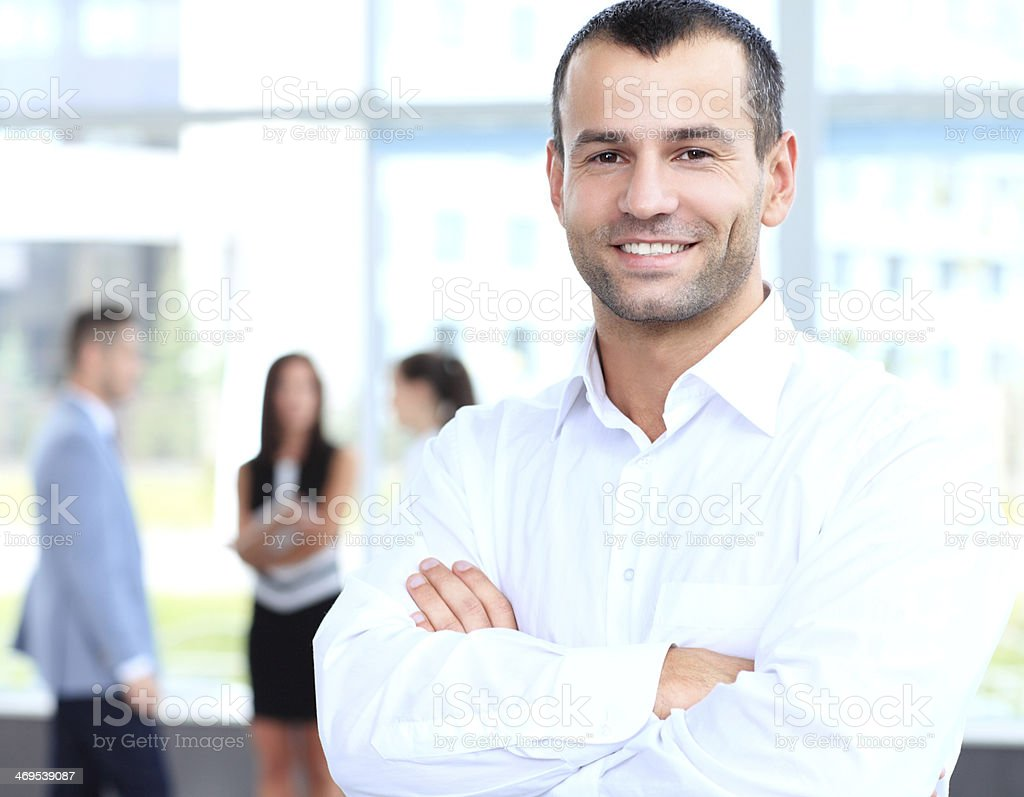 Cross-armed leader looking at camera in working environment stock photo