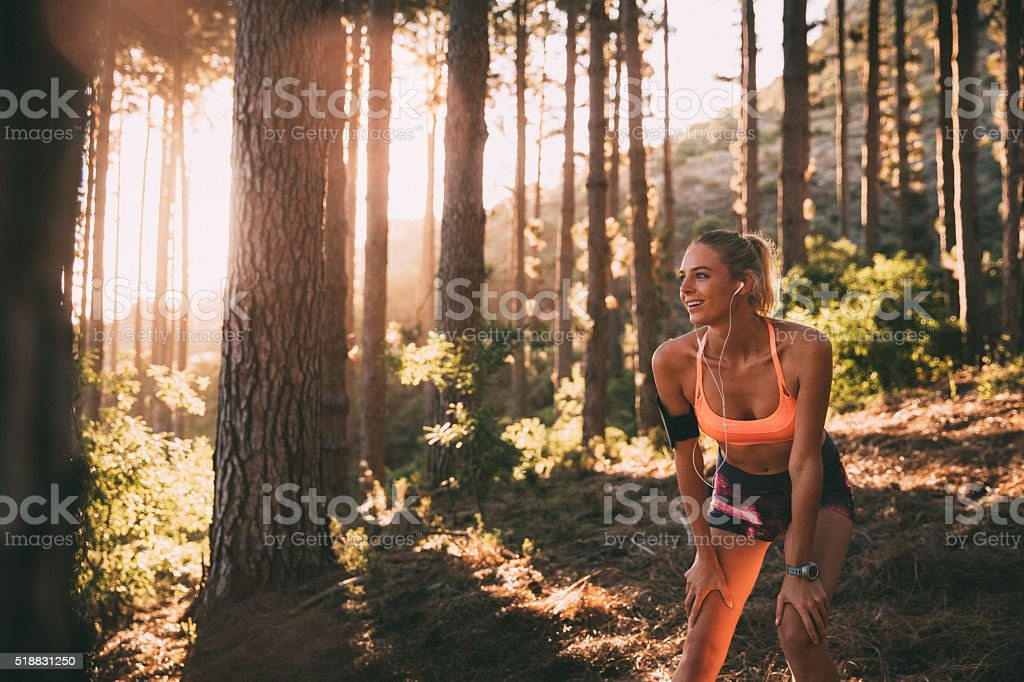 Cross-country runner resting on a morning trail run on mountain stock photo