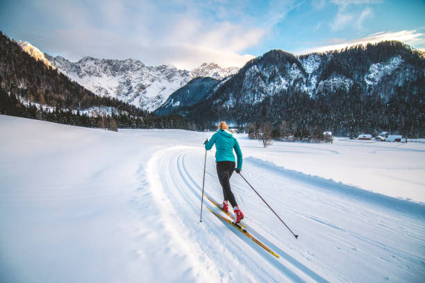 Cross-country skiier gliding on the slopes stock photo