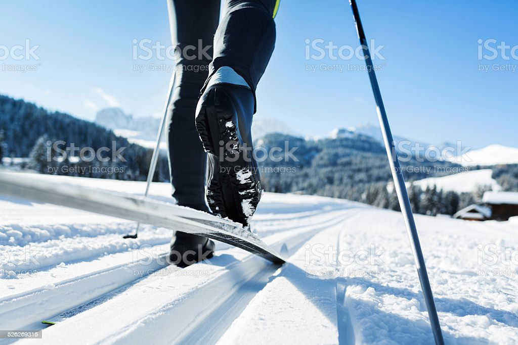 Close-up of a mans legs doing cross-country skiing in dolomites.