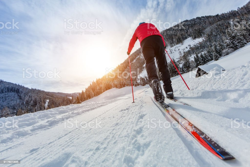 Cross-country skiing. Young man doing outdoor exercise. stock photo