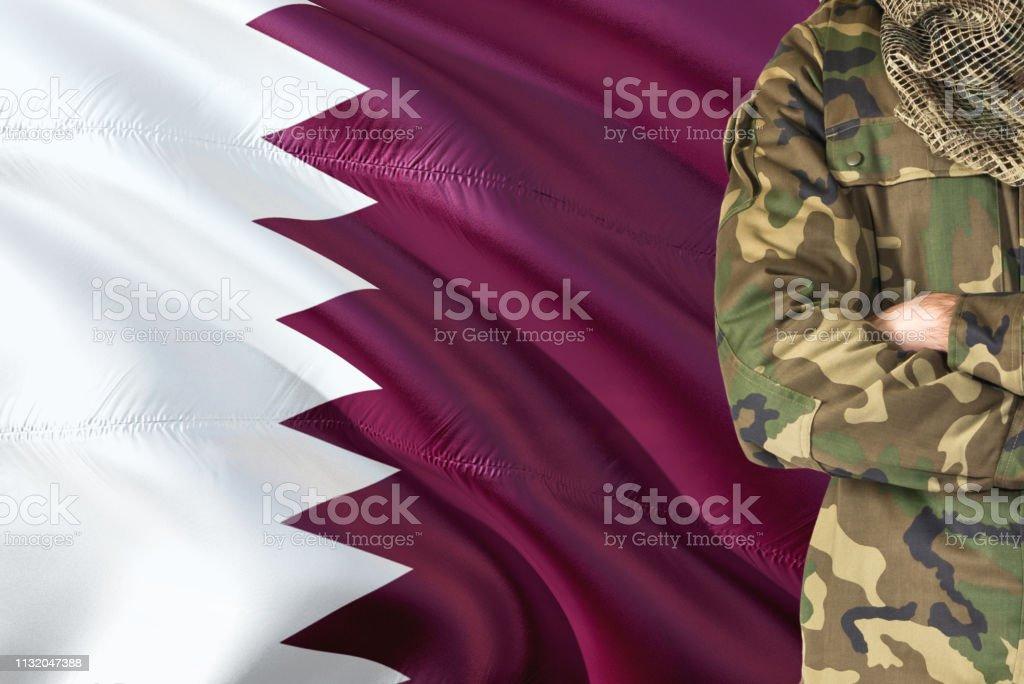 Armas cruzadas soldado qatarí con bandera nacional agitando en el fondo-Qatar tema militar. - foto de stock