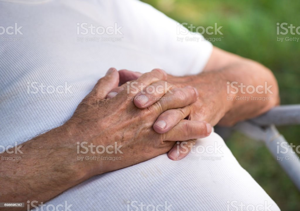 Crossed hands of old man stock photo