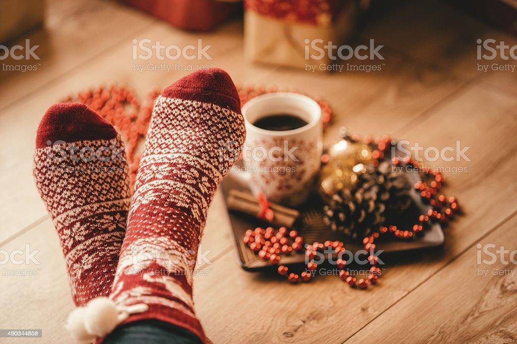 Crossed legs in seasonal winter socks stock photo