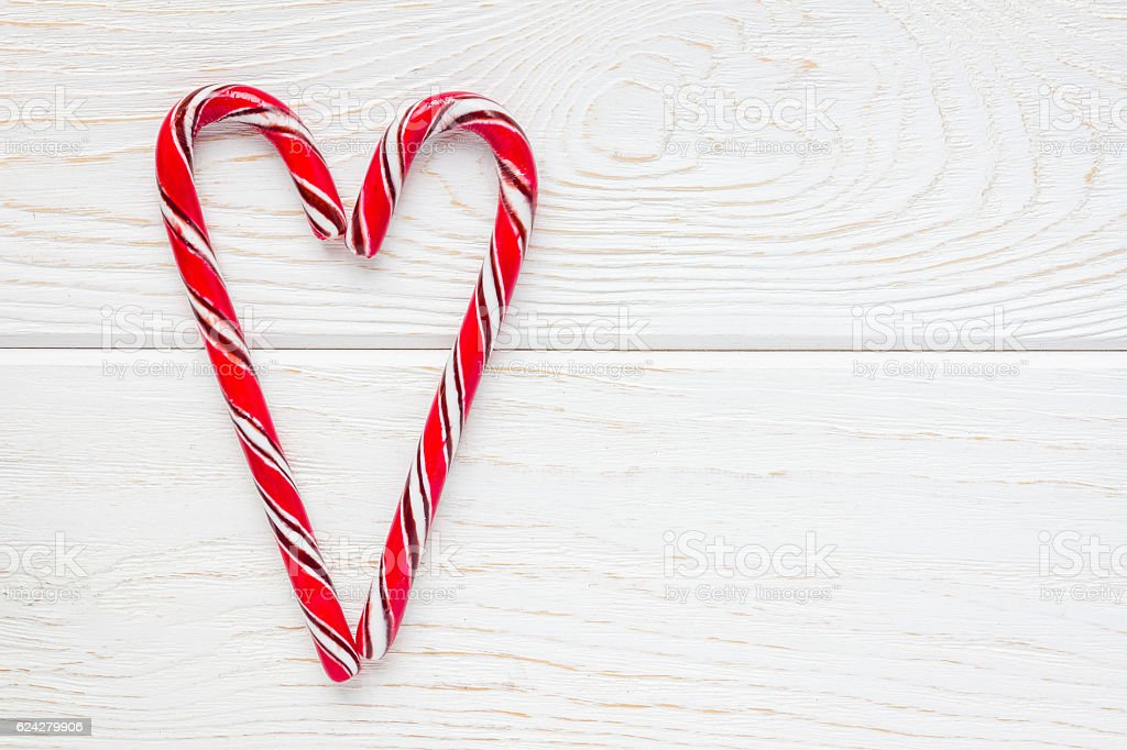 Crossed peppermint candy canes on white wooden background stock photo
