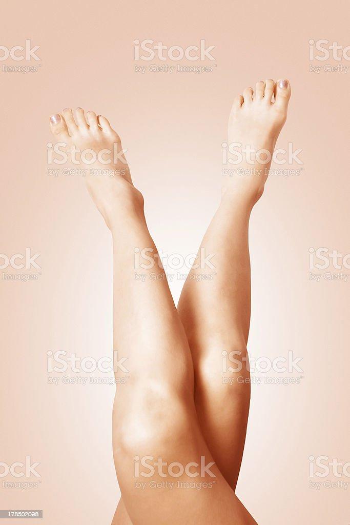 Crossed suntanned female legs royalty-free stock photo