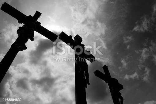 Three crosses in black and white in front of a dramatic sky with clouds The location ist a punlic place on a mountain in germany