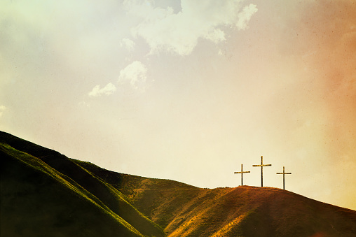 A depiction of the crucifixion of Jesus Christ, three crosses on a hill. Imagery intended to represent the crucifixion and resurrection of Jesus Christ celebrated on Easter sunday. Horizontal image with copy space.