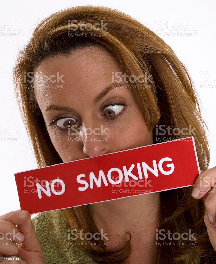 Cross-eyed woman holds 'No Smoking' sign royalty-free stock photo