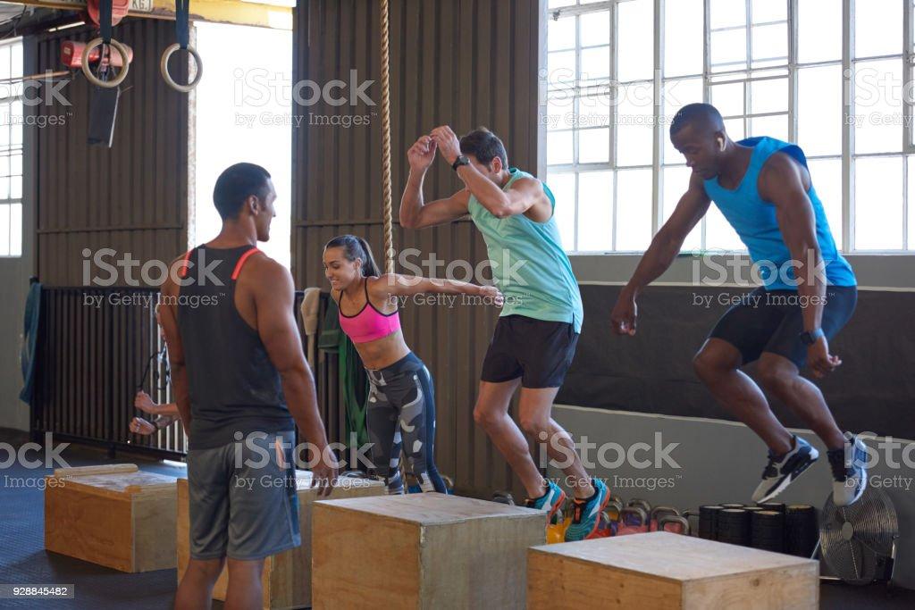 CrossFit Klasse springen auf Holzkisten, geleitet von trainer – Foto