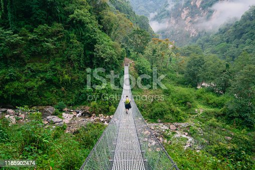A rear-view shot of a caucasian male tourist standing next to a suspension bridge mid way through a Trek to Annapurna Base Camp in Nepal.