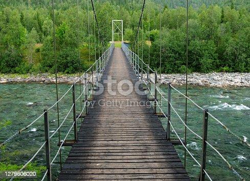 Crossing A Wooden Pedestrian Suspension Bridge Over River Ranaelva Near Mo I Rana Norway On A Cloudy Summer Day