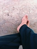 This photo is contain one person who crossing barefoot on a floor.