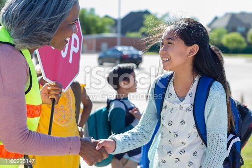 Caring mature female crossing guard shakes a preteen girl's hand.