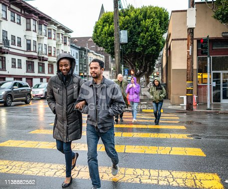 A couple followed by a larger group of pedestrians, crossing the street at a San Francisco intersection during the rain.