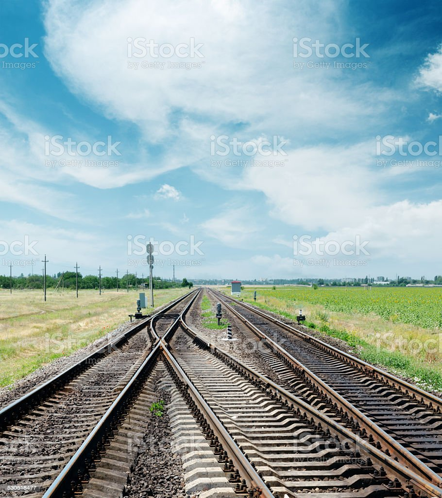 crossing of railroad under cloudy sky stock photo