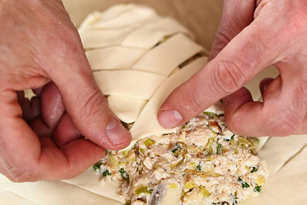 Crossing pastry stripes over each other to enclose filling Crossing pastry stripes over each other alternately to enclose filling. Making Chicken, Cheese and Leek Parcel Series. alternately stock pictures, royalty-free photos & images