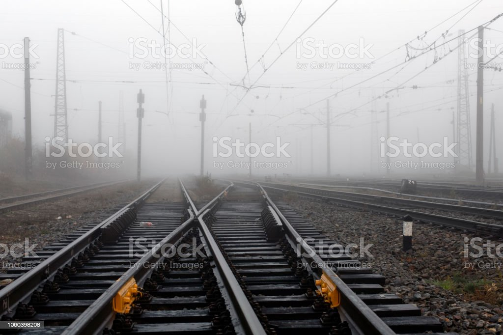 Crossing railways disappearing in the mist in autumn morning stock photo