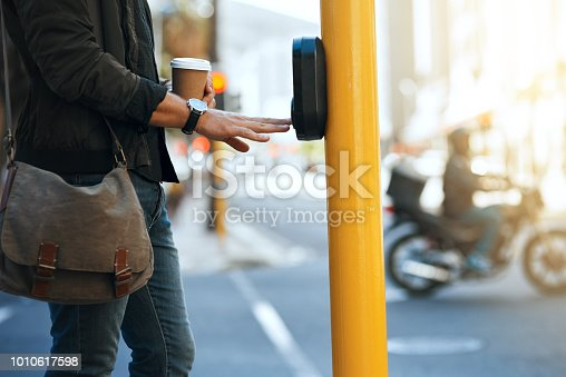 Cropped shot of an unrecognizable man pressing the crosswalk button on a traffic light while traveling through the city