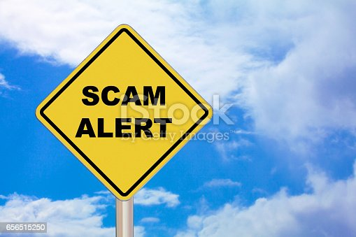 """Diamond-shaped crossing sign with yellow background and black border with """"Scam Alert"""" written in the middle."""