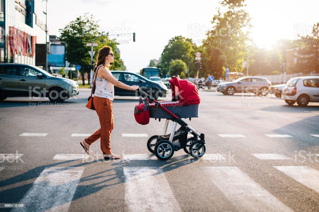 Cruzar el bulevar, con bebés en cochecitos de bebé con mucho tráfico en hora punta - foto de stock