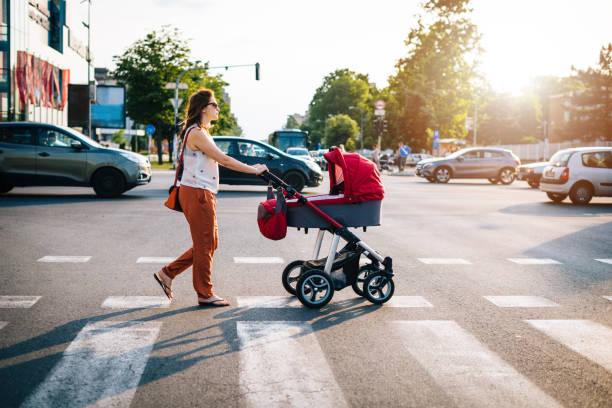 Crossing the boulevard with baby in prams with heavy traffic in rush hour stock photo
