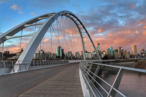 Crossing The Bridge At Sunset Walking across the Walterdale Bridge in Edmonton towards downtown at sunset. alberta stock pictures, royalty-free photos & images