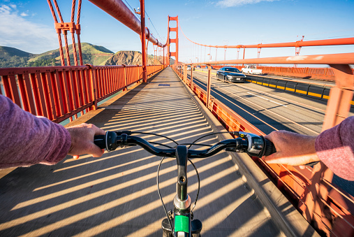 A personal perspective of a biker crossing the iconic Golden Gate Bridge in San Francisco, California, as cars cross the bridge in the distance.