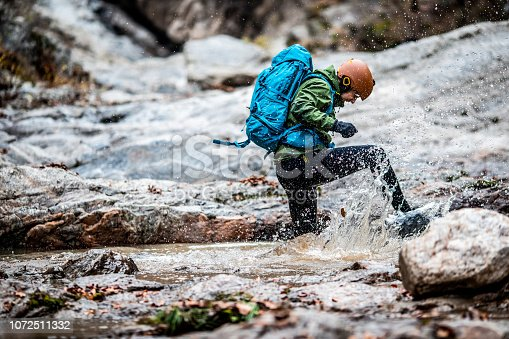 Man is crossing the river by jumping and running and its difficult to cross it