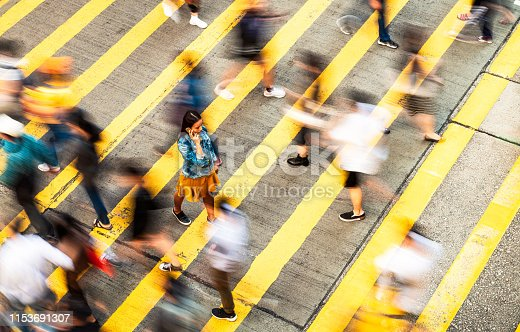 Motion blur as people cross the street at a zebra crossing, while a woman slowly walks, as she talks on the phone.