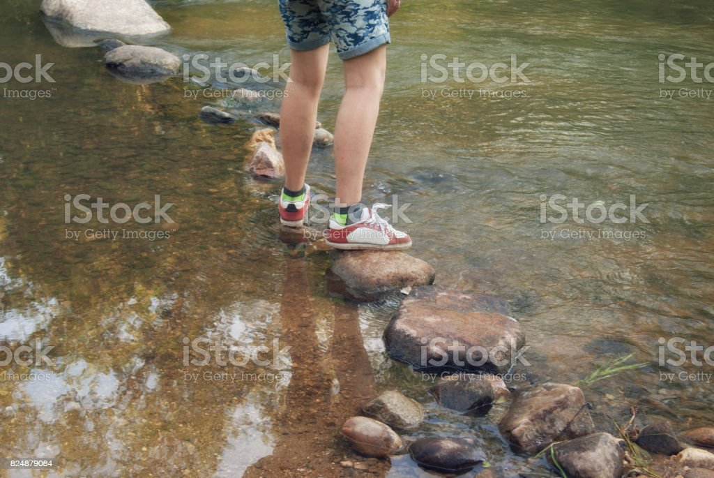 Crossing the rocks through the water flow of a mountain stream stock photo