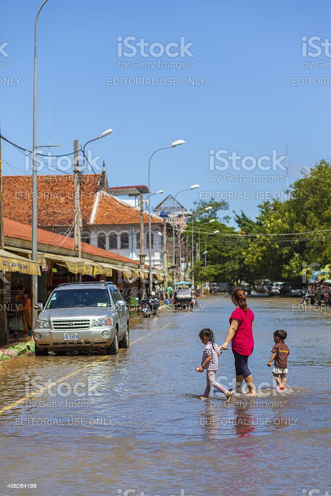 Crossing the street in floodwaters, Siem Reap, Cambodia stock photo