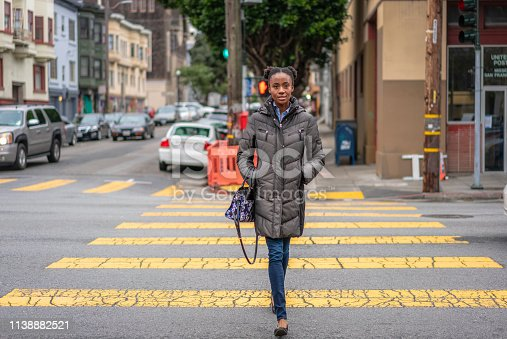 A woman on a crosswalk during winter in San Francisco, California.