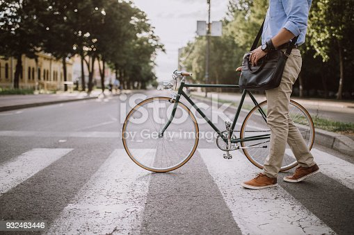 Handsome young businessman with bicycle in the city