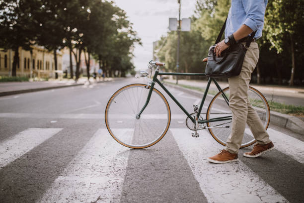 crossing the street with the bicycle - cycling stock photos and pictures