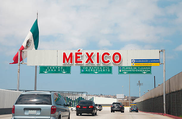 Crossing the Us - Mexico border to Tijuana A view of the highway entrance to Tijuana Baja California at the international US Border with Mexico in San Diego. geographical border stock pictures, royalty-free photos & images