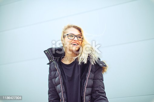 Cross-processed Late teen Portrait outdoors against uniform background
