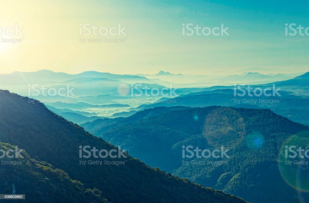 cross-processed view of sunrise over mountain range stock photo