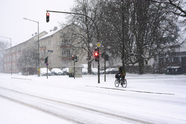A Crossroad in Snowy day In a snowy day, a girl is riding a bicycle across a crossroad. The traffic light is red. erlangen stock pictures, royalty-free photos & images
