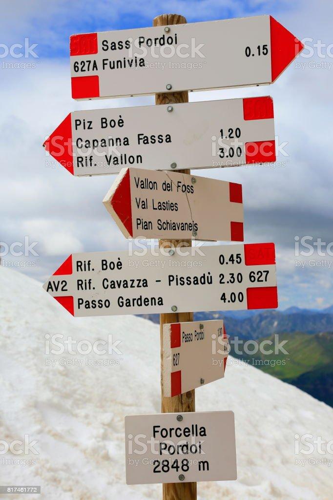 Crossroads directions set sign pointing above Idyllic Sas Pordoi and Passo Sella, Langkofel pinnacle massif mountain range front view at sunrise, dramatic and majestic Dolomites, Italy tirol alps stock photo