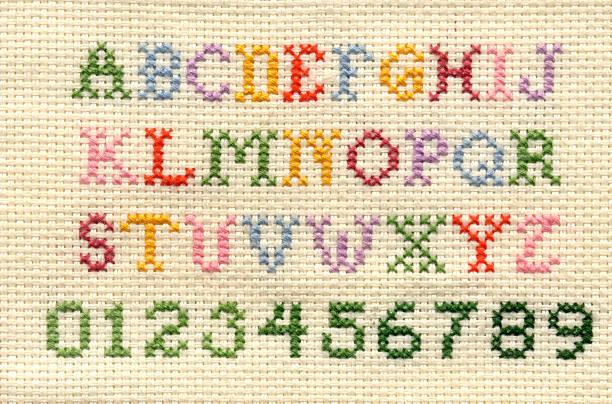 Punto de cruz alfabeto y números - foto de stock