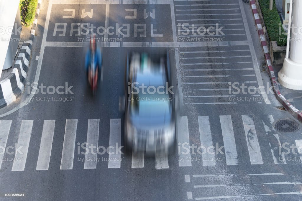 Crosswalk and car, Busy city street and car in motion blur on...
