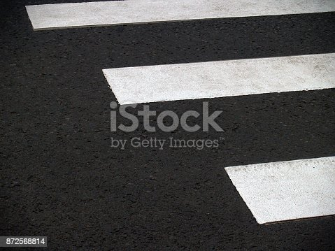 Aaging scratched corrugated asphalt with crosswalk markings