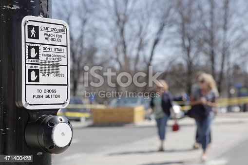 Close up, rack focus of a crosswalk sign and button. A red, blurred car drives by.