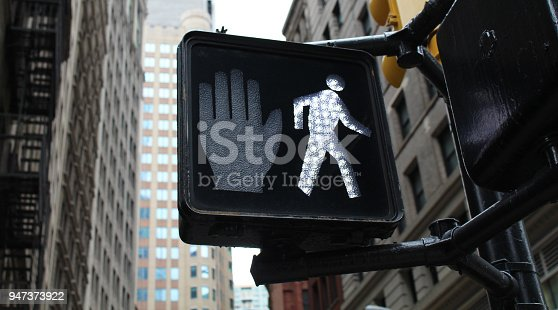 NYC crosswalk sign with walk icon illuminated and city buildings in background