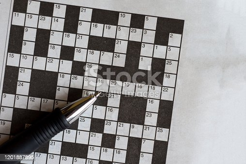 Crossword puzzle from newspaper with a pen to fill in answers