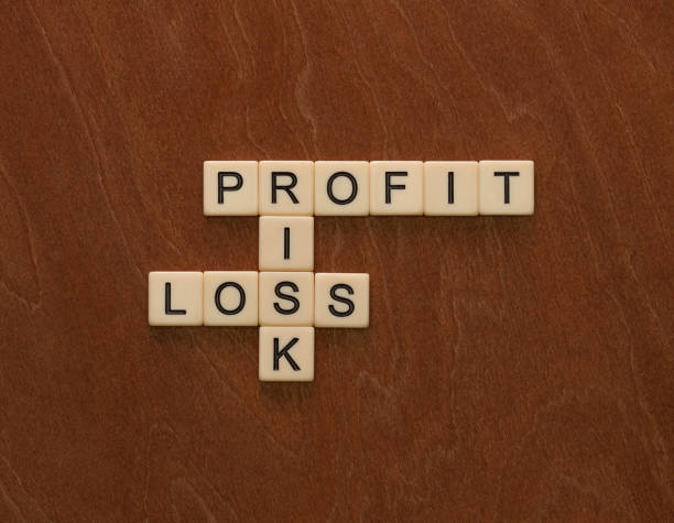 crossword puzzle with words risk, profit and loss. risk management concept. - word game stock pictures, royalty-free photos & images
