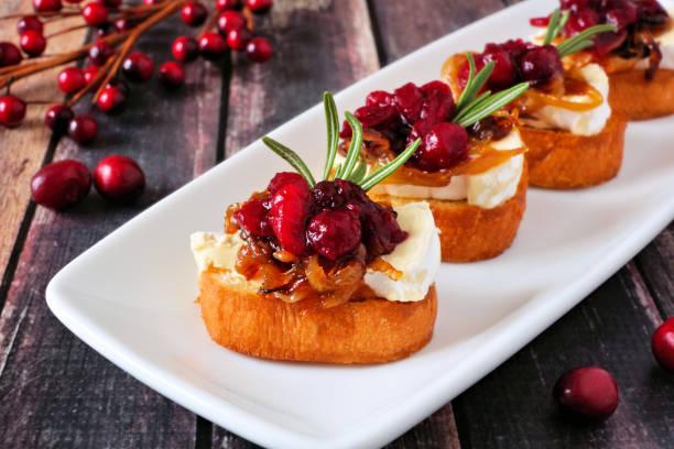 在盤子裡放在一塊與木材上的紅莓、魚和焦糖洋蔥的 crostini 開胃菜 - 開胃菜 個照片及圖片檔