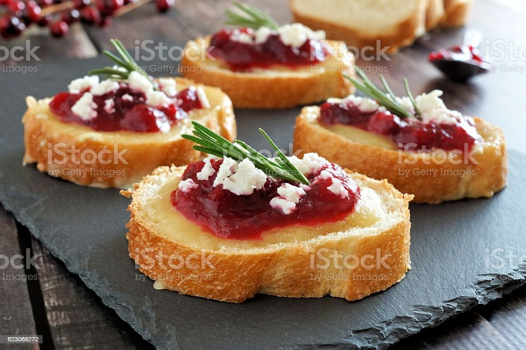 Crostini appetizers with cranberry sauce, cheese and rosemary on slate - foto stock